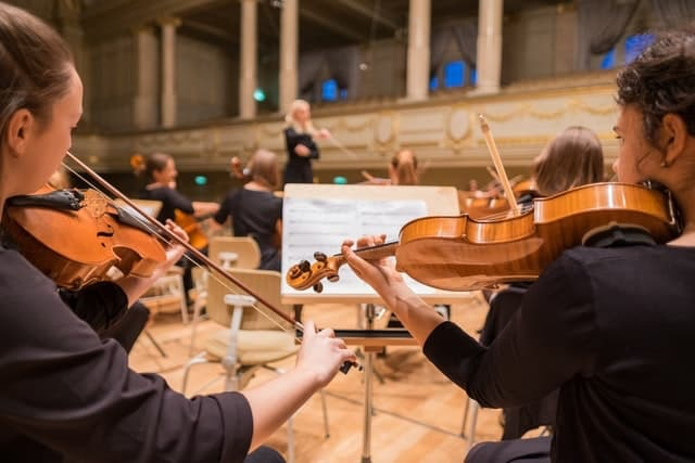 Orchestra of musicians with conductor in background, photo by Manuel Nägeli on Unsplash